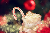 Girl holding cacao with whipped cream and peppermint candy cane. Christmas holiday concept. Holiday background. Holiday or winter background. Horizontal,  with fantasy stars bokeh