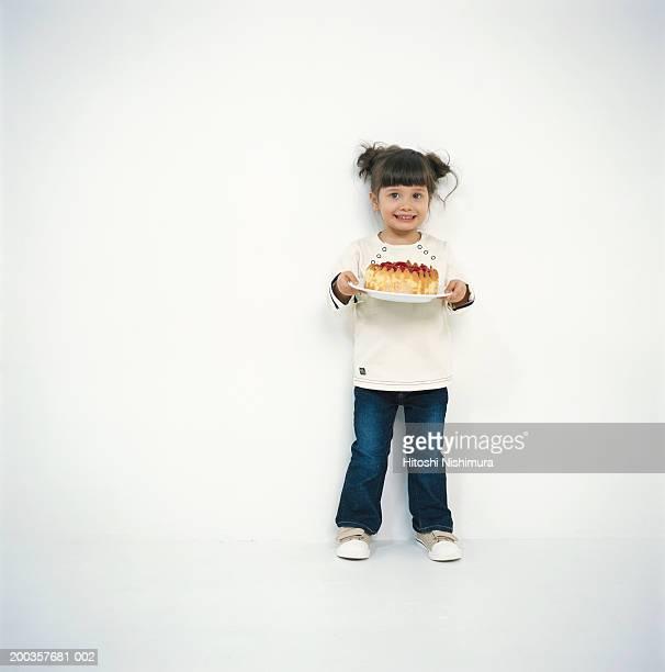 Girl (4-5) holding cake, smiling, portrait