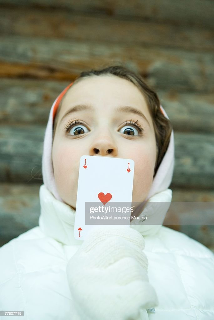Girl holding card over mouth, dressed in winter clothing, looking at camera, wide eyes