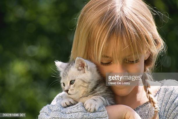 Girl (6-9) holding cat