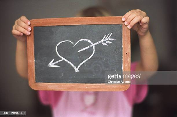 Girl (2-4) holding chalk drawing of arrow through heart