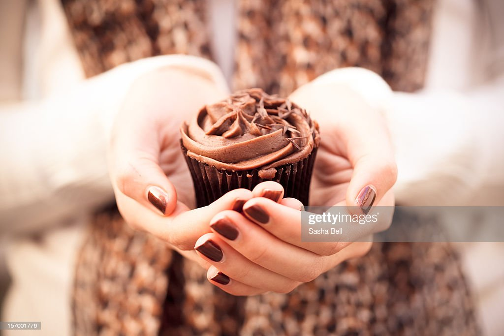 Girl holding chocolate cupcake in hands : Stock Photo