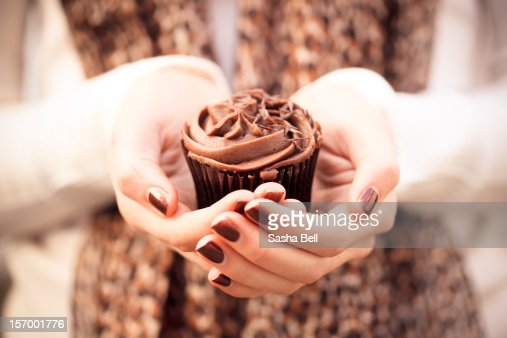 Girl holding chocolate cupcake in hands : Stock-Foto