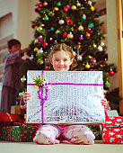 Girl (5-7) holding christmas present, smiling, portrait