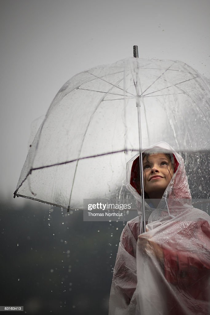 Girl holding clear umbrella looking at rain : Stock Photo