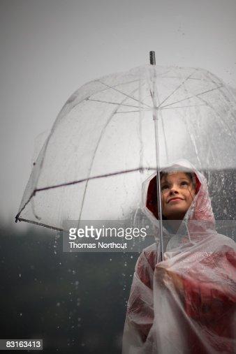 Girl holding clear umbrella looking at rain : Stock Photo