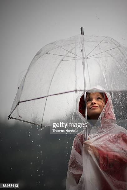 Girl holding transparente modelo mirando a la lluvia