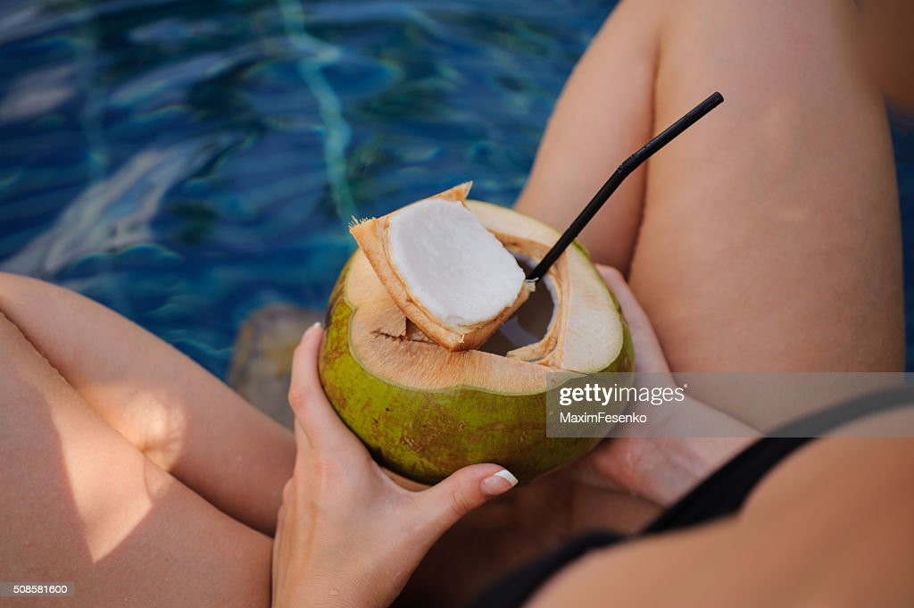 girl holding coconut in swimming pool : Stock Photo
