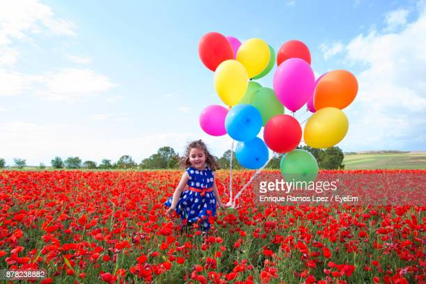 Girl Holding Colorful Balloons While Standing On Field Against Sky