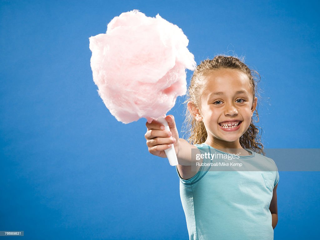 Girl holding cotton candy smiling