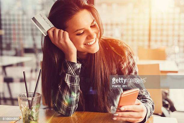 Girl holding credit card and texting