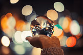 Girl in city holding crystal ball with beautiful bokeh