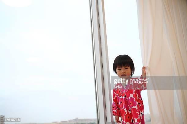 Girl holding curtain