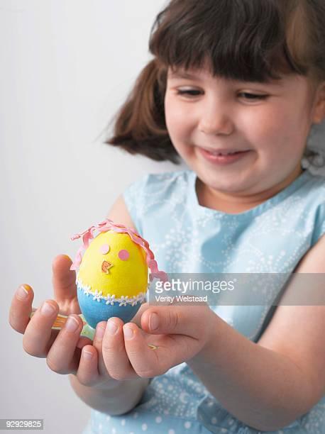 Girl holding decorated Easter egg