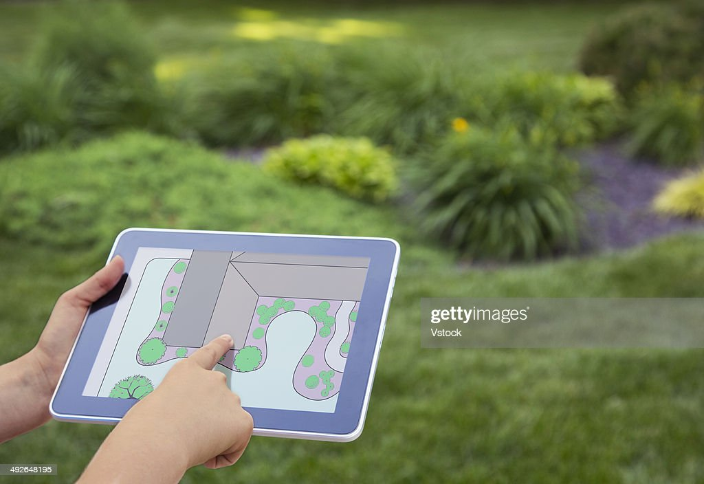 Girl (12-13) holding digital tablet with garden plan