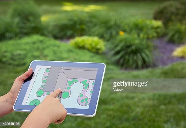Girl (12-13) holding digital tablet with garden plan