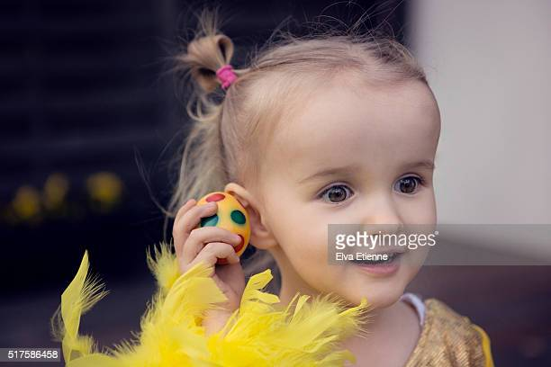 Girl (3-4) holding Easter egg to ear