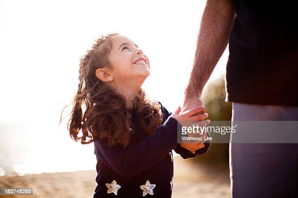 Girl holding father's hand, looking up