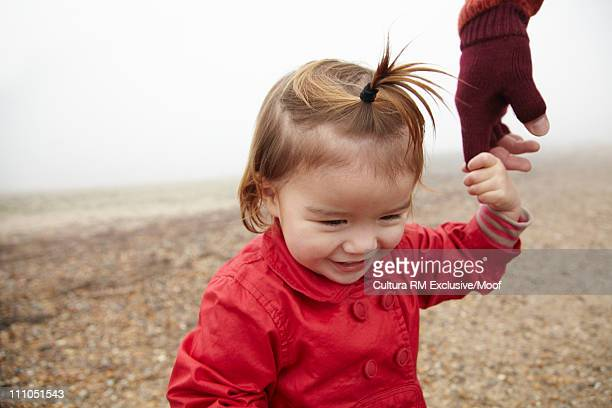 Girl holding fathers hand on the beach