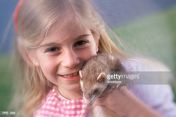 Girl holding ferret, smiling