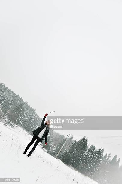 Girl holding firework in field of snow