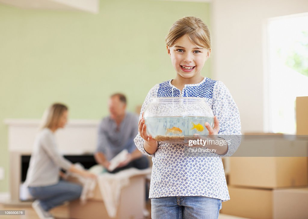 Girl holding fish bowl in her new house : Stock Photo