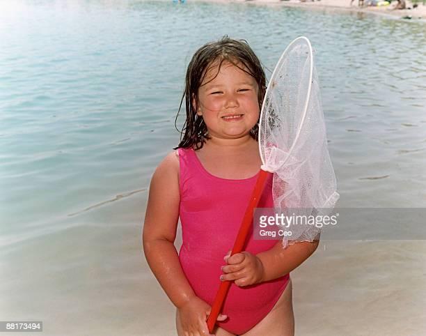 Girl holding fishing net by lake