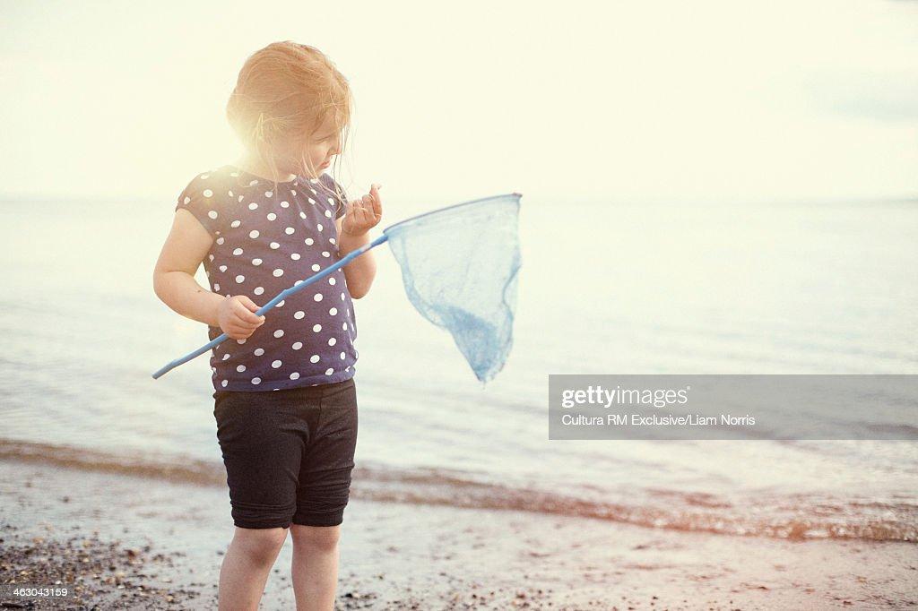 Girl holding fishing net on beach : Stock Photo
