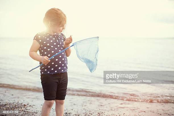 Girl holding fishing net on beach