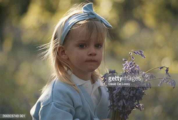 Girl (3-4) holding flower outdoors, portrait, close-up