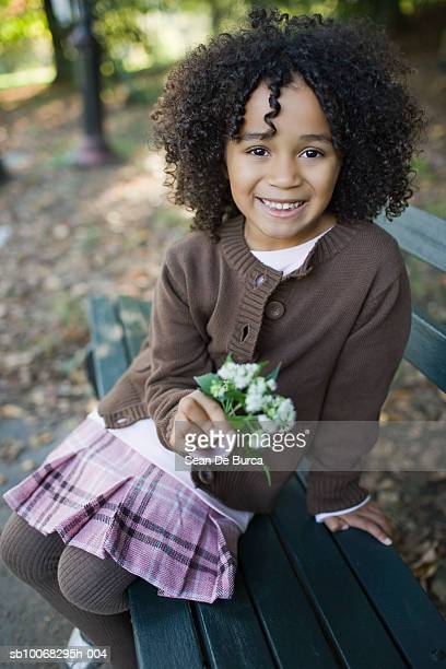 Girl (4-5) holding flower, smiling, portrait, close-up