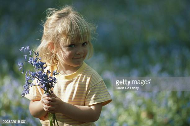 Girl (4-5) holding flowers in field, portrait