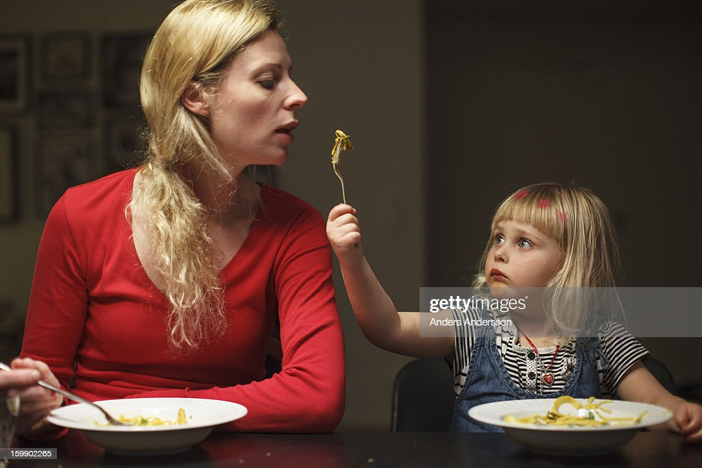 Girl holding fork w food to mother : Stock Photo