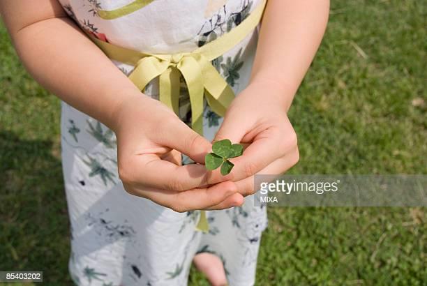Girl holding four-leaf clover