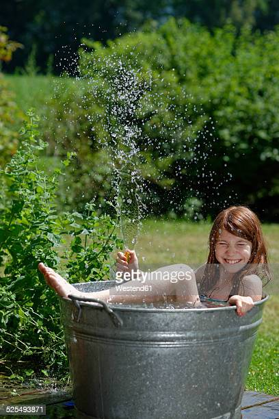 Girl holding garden hose while bathing in a zinc tub