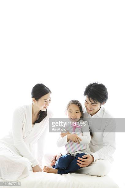 girl holding gift box with parents