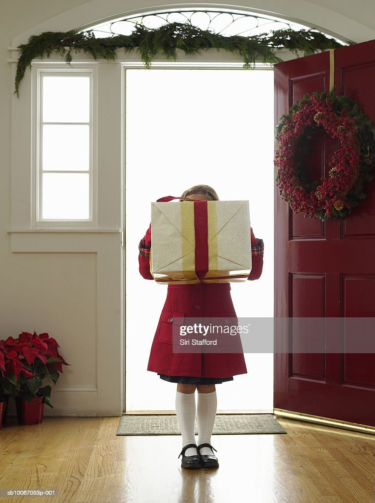 Girl (6-7) holding gift in front of face : Stock Photo