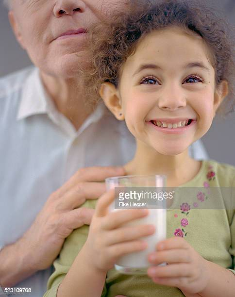 Girl Holding Glass of Milk and Smiling