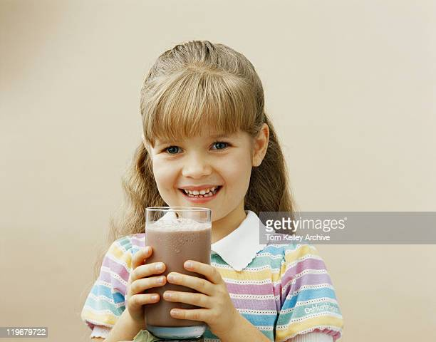 Girl holding glass of milkshake, smiling, portrait