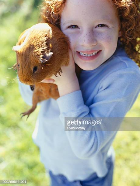 Girl (6-7) holding guinea pig, close-up