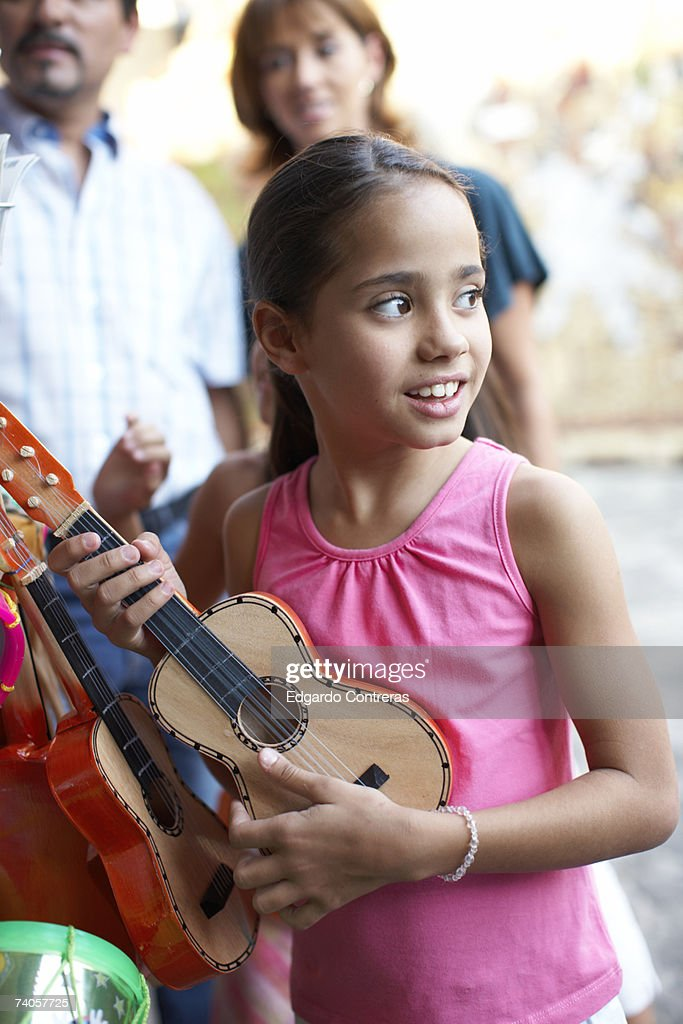 Girl (8-9) holding guitar, outdoors : Stock Photo