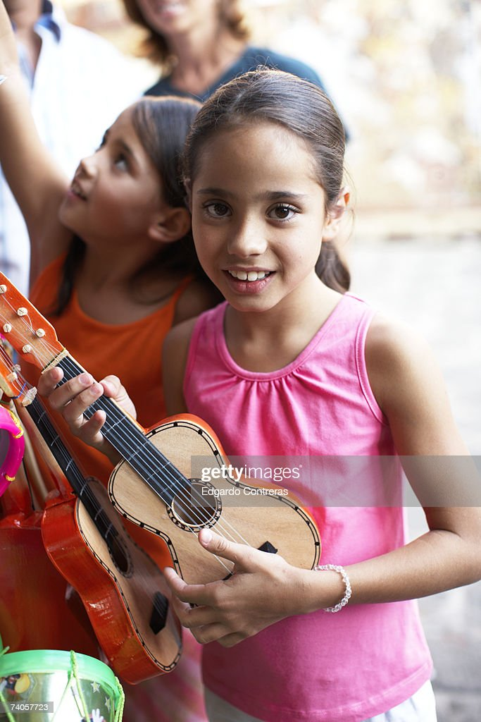 Girl (8-9) holding guitar, outdoors, portrait : Stock Photo