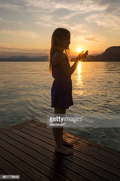 Girl holding hands against the sun at sunset