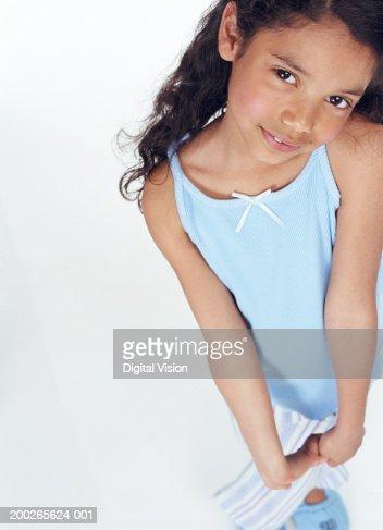 Girl (6-8) holding hands together, smiling, portrait : Stock Photo
