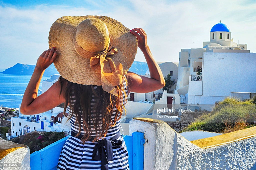 Girl holding hat in Oia Greece : Photo