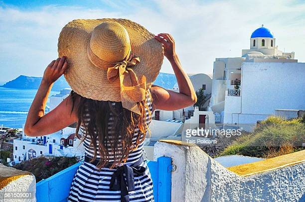 Girl holding hat in Oia Greece