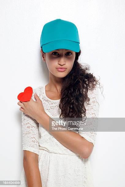 Girl holding heart shaped ring looking at camera