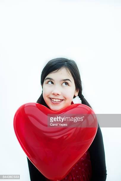 Girl holding heart-shaped balloon