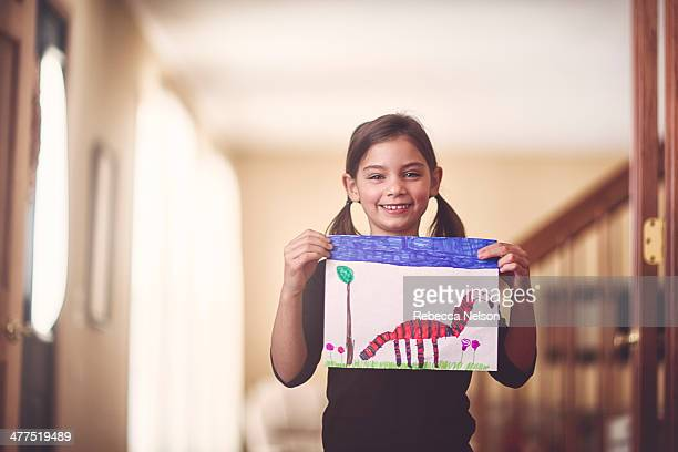 girl holding her drawing of an imaginary animal