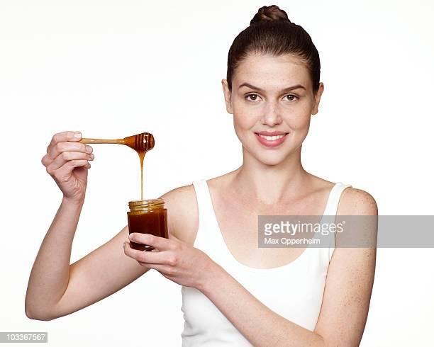 girl holding honey dipper above honey jar